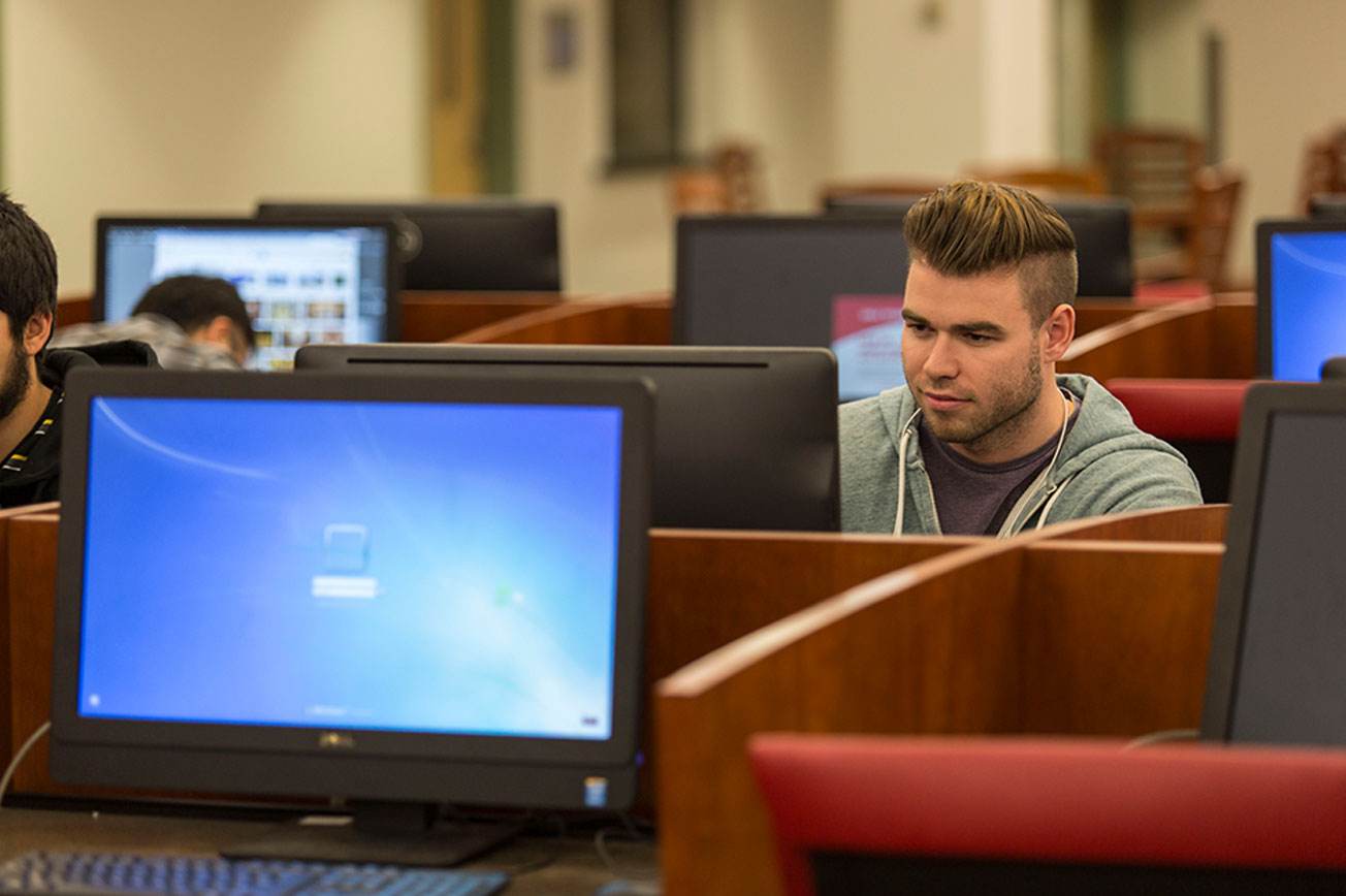 A male student stares intently at a computer screen.
