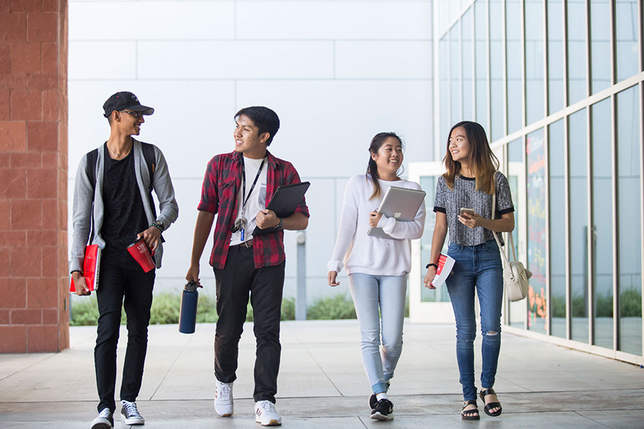 Four students side-by-side walking and smiling.