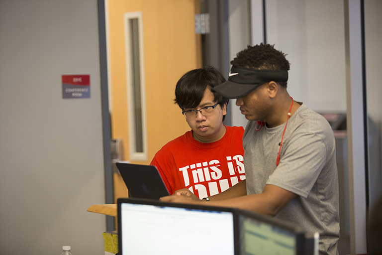 Two male students look at a tablet.