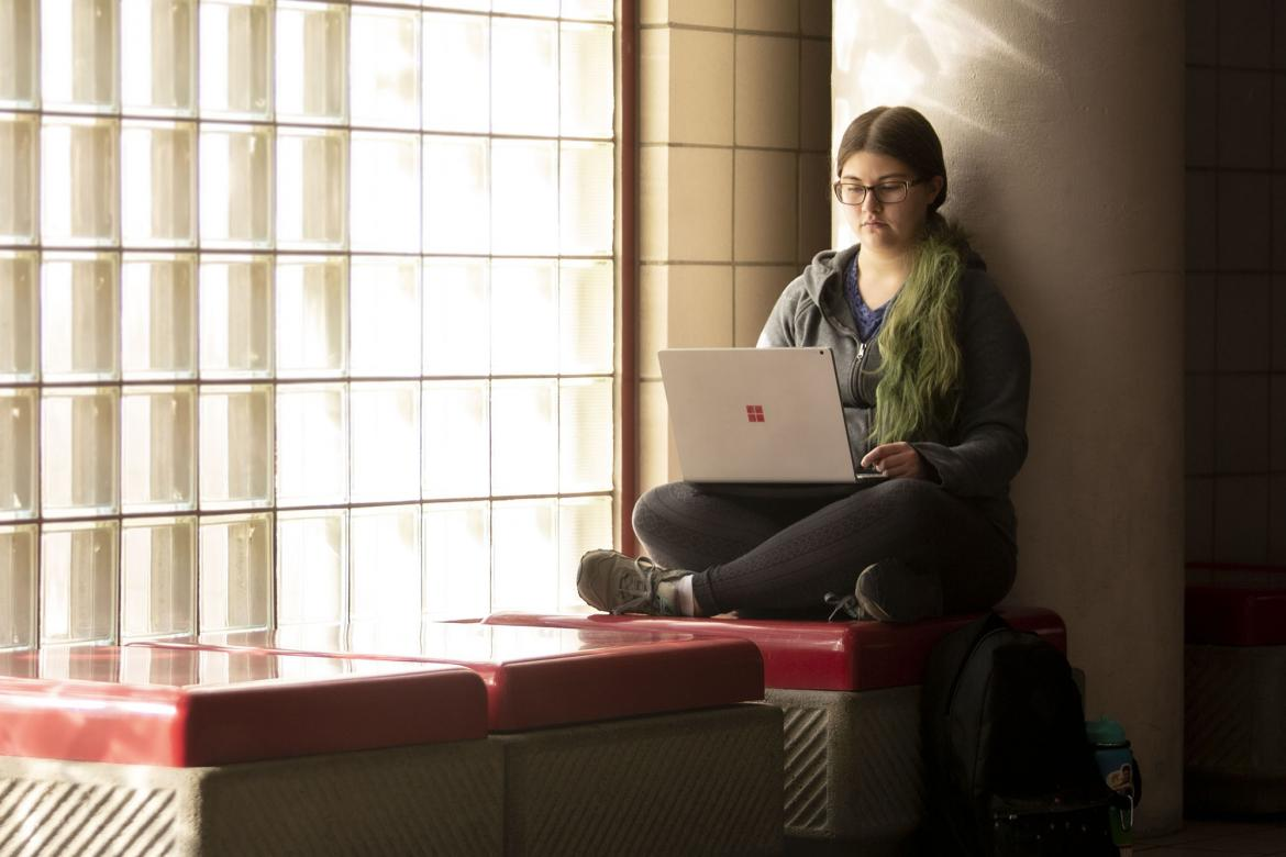 "alt=""A female student gazes down at her laptop."""