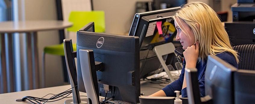A female student employee fields calls at a U-N-L-V help desk.
