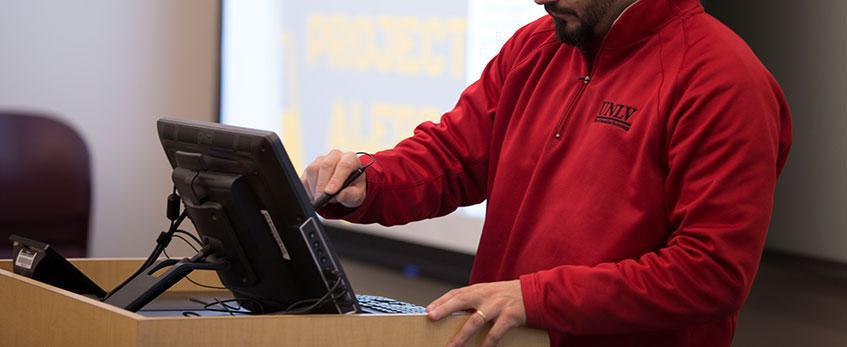 A male staff member standing at a lectern sets up classroom technology.